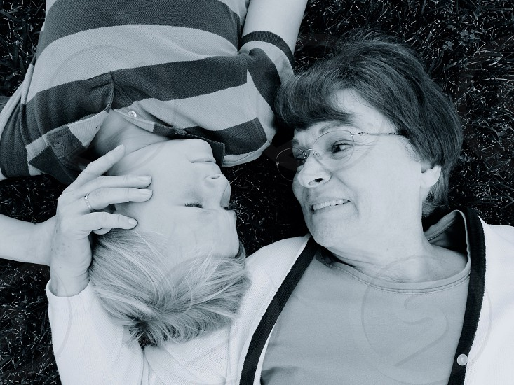 mother and son lying on grass field photo