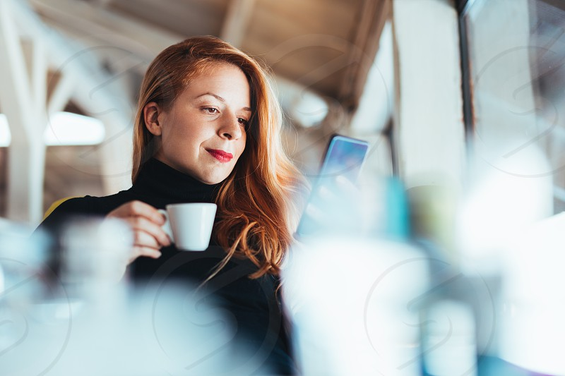 Young woman using smartphone in a cafe photo