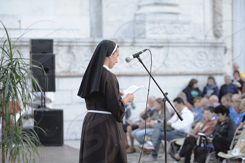 nun on stage in front of microphone photo