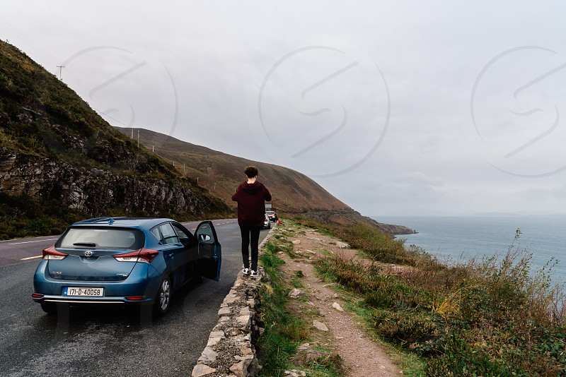 Woman looking at the seascape with car on Irish road. Ring of Kerry photo