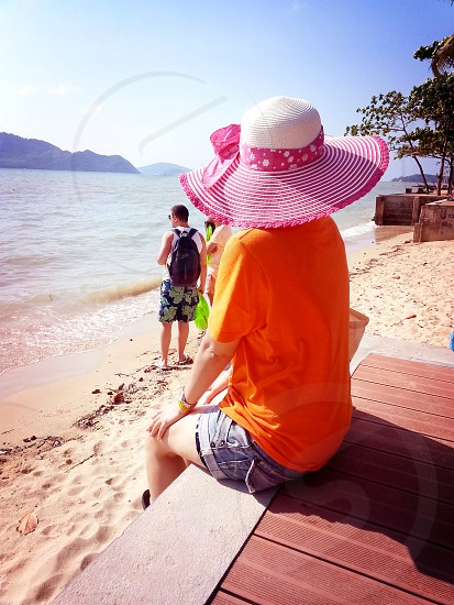 woman wearing red t shirt and blue daisy dukes sitting on brown wooden surface near beach during daytime photo