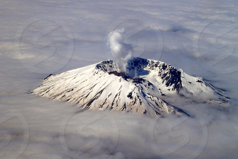 erupting snow covered volcano photo