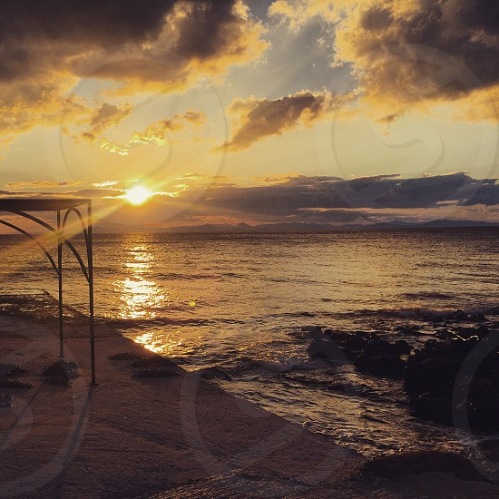 Sunset sea waves Greece riviera beach sky clouds photo