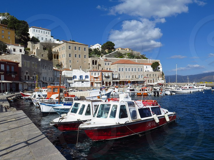 Daytime view of boats in Hydra Island Greece. Blue sky travel travel to europe ocean harbor photo