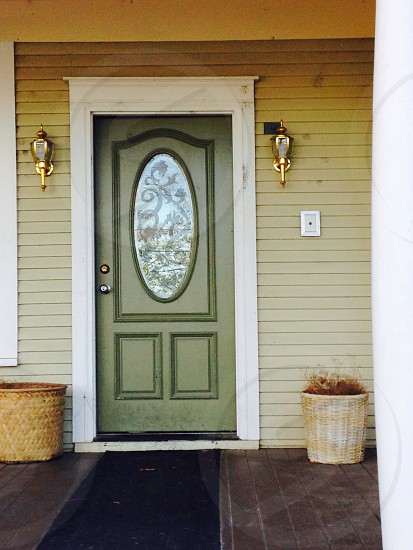 green wooden door with white frame photo