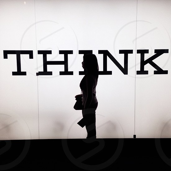 silhouette of standing woman by white wall with black think print photo