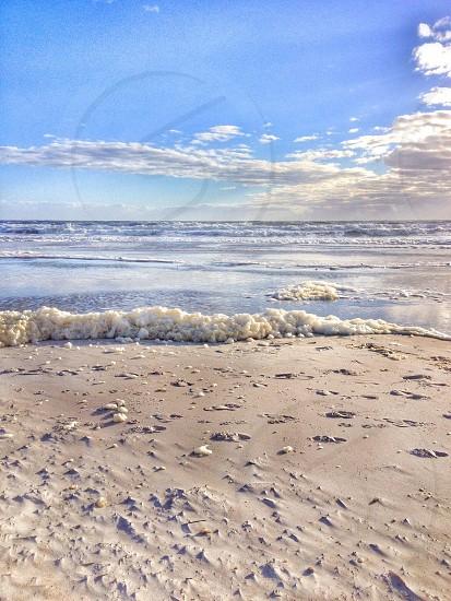 view of grey sand on sea seashore photo