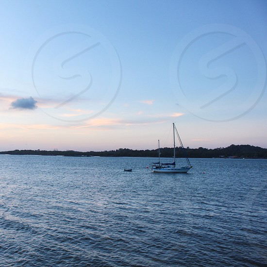 white motorized boat on body of water under cloudless sky during golden hours photo