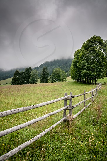 wood post fence in green field photo