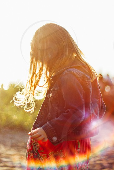 girl in blue denim jacket standing in front of sun rays photo