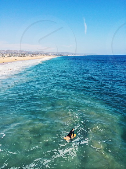 person on an orange surfboard in the blue sea photo