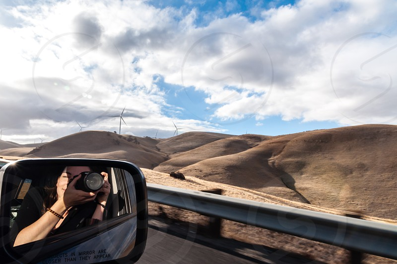 Photographer reflected in side mirror of car taking photos of rolling golden hills photo
