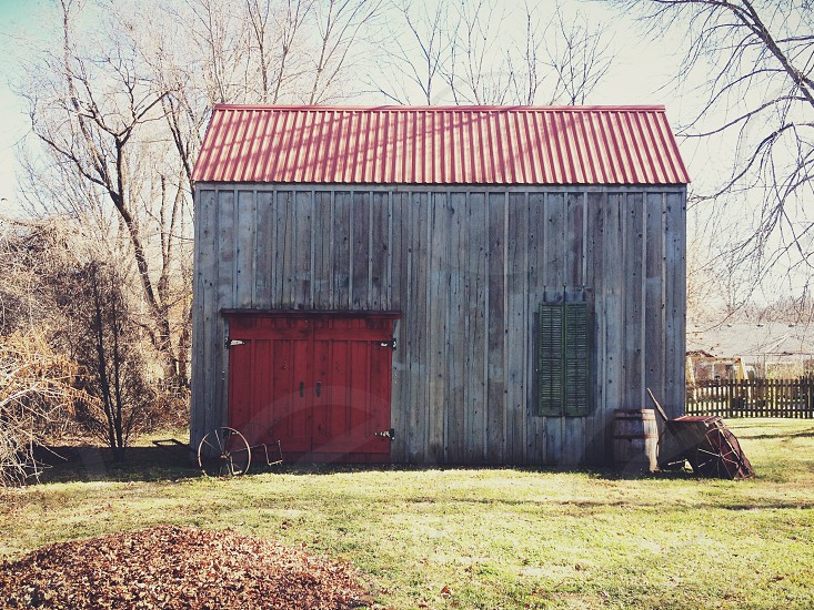 brown wooden barn with red painted door and roof photo