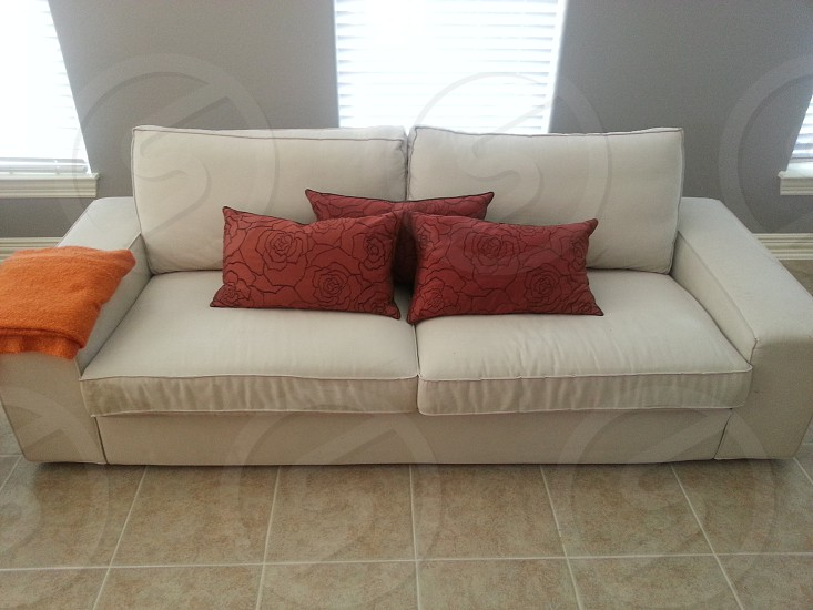 Ikea sofa with orange throw and red pillows photo