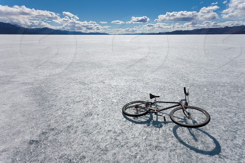 Bike on ice surface of huge frozen Lake Laberge Yukon Territory Canada in April photo