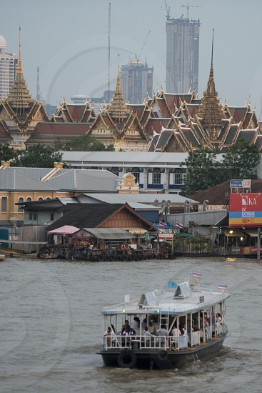 The Boat trafic in front of the Royal Palace and Wat Phra Kaew at the chao phraya river in the city of Bangkok in Thailand.  Thailand Bangkok November 2017 photo