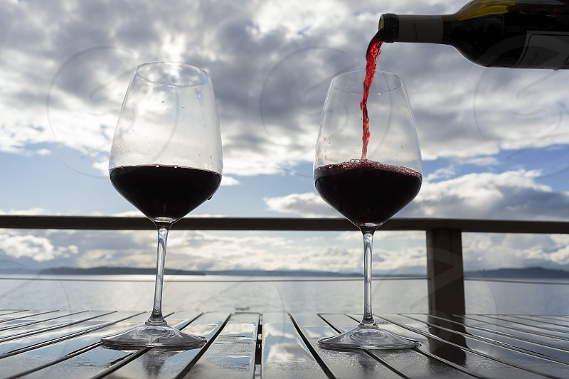 Pouring red wine on a sea view deck table. photo