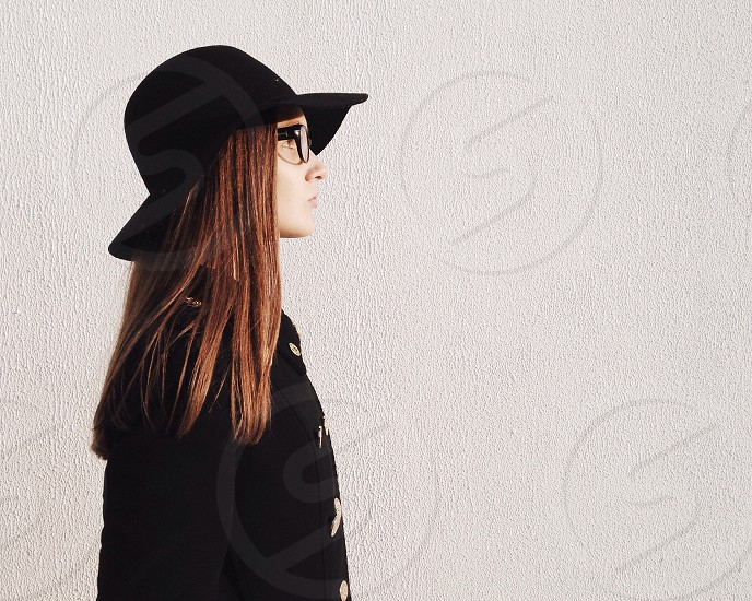 woman with brown short hair in black jacket standing near white wall photo