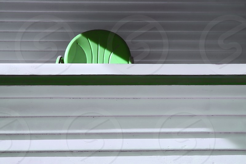 Green back of a metal chair  peaks out from  the edge of the gray porch rail photo
