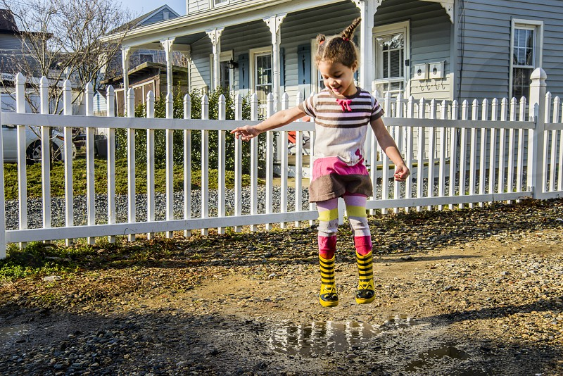 girl wearing black and white striped t-shirt and yellow boots jumping over the water puddle during daytime with building in background below bright sky during daytime photo