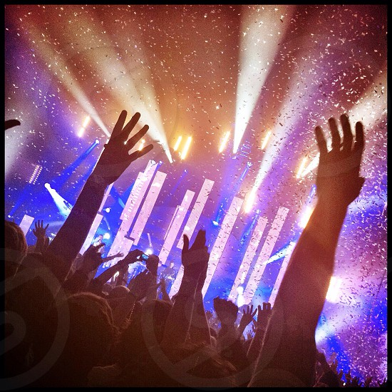 Audience members at a concert throw their hands up in the air while ticker tape and dramatic lighting add to the atmosphere.  photo