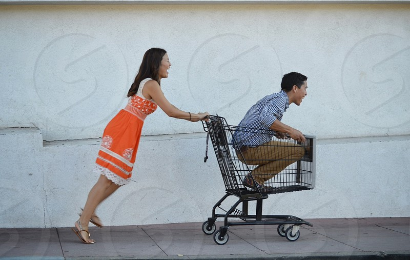 woman in orange dress pushing a man in a shopping cart photo