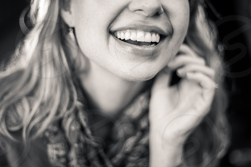A beautiful young woman with long strawberry blond hair earrings and a colorful paisley scarf smiling in front of a clean dark background. B&W photo