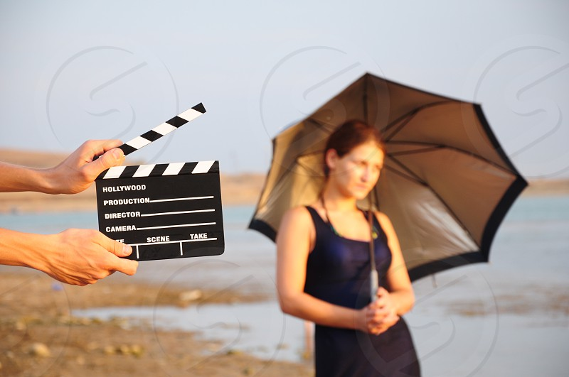 person holding black and white director's cut board by a woman in black scoop neck tank under black and grey umbrella on a brown sandy beach under blue sky photo