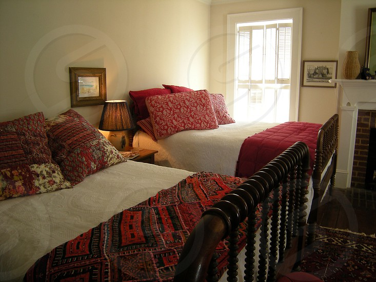 Two beds in bed and breakfast room with white and red linens photo