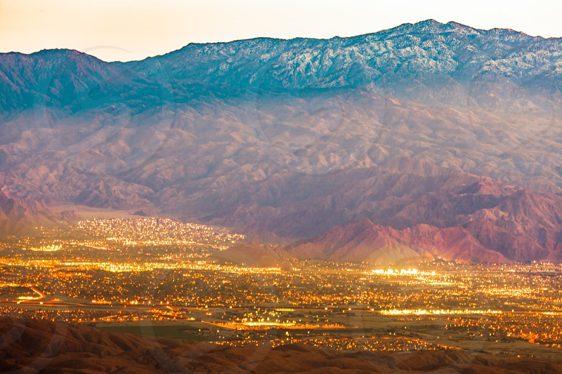Night lights of resort city of Palm Springs with Mt. San Jacinto Mountains behind urban area in Coachella Valley Mojave Desert of Southern California US after sunset photo