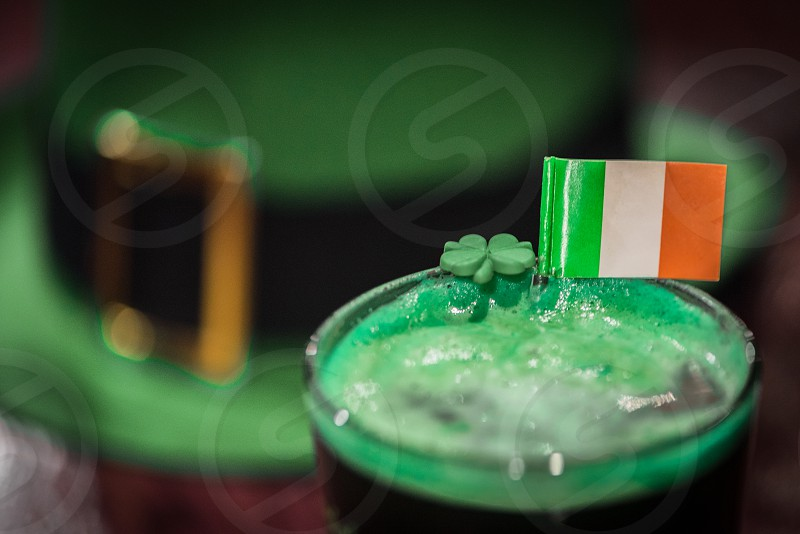 Glass of green beer with a shamrock and Irish flag sitting on a bar in a pub with a green leprechaun hat blurred out in the background. photo