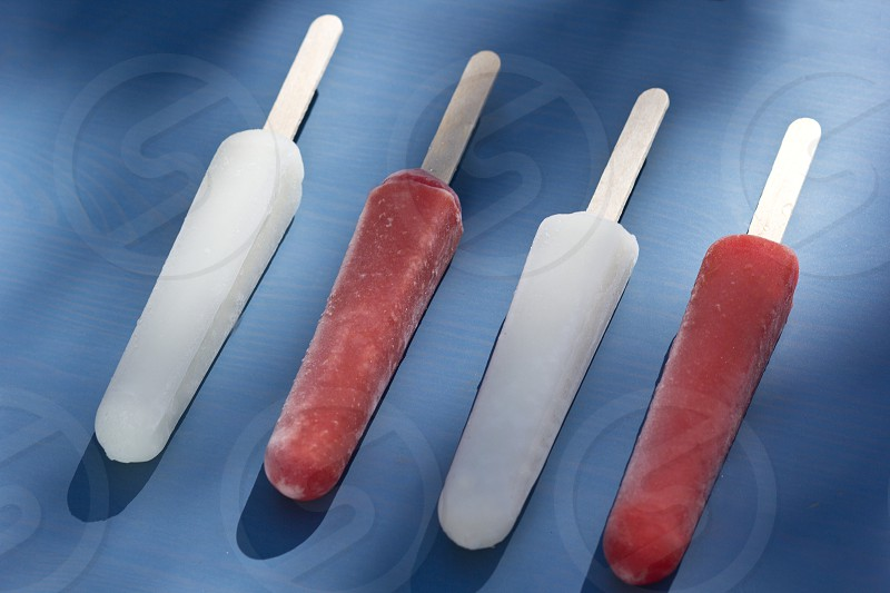 four popsicles laying diagonally on a blue background photo