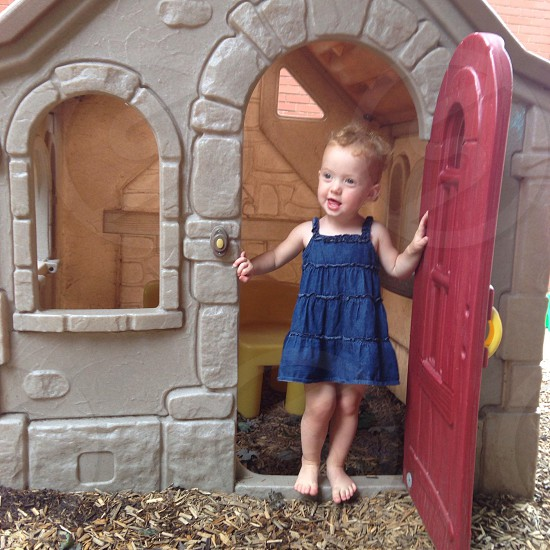 girl in blue dress standing at the door of the playhouse photo