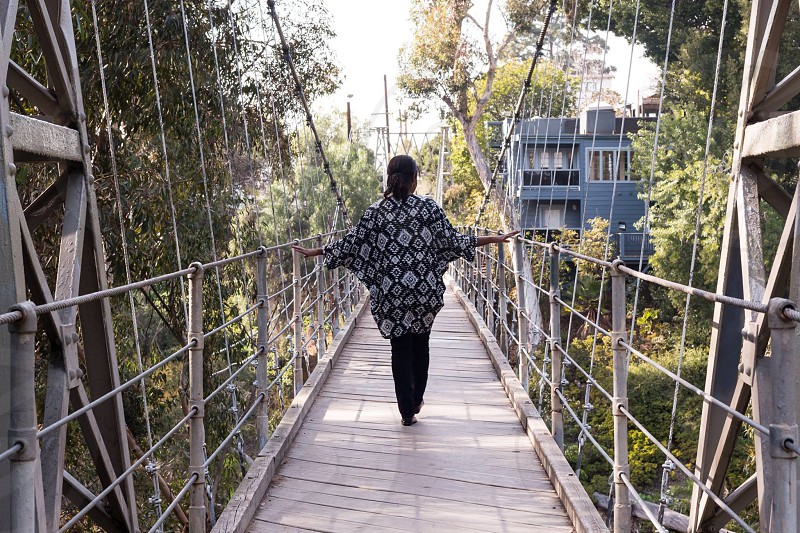 woman in back and white long sleeved midi dress walking on gray concrete bridge during daytime photo