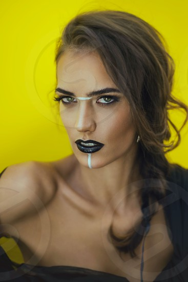 yellow background young female woman girl model brunette naked shoulders exotic futuristic sci fi makeup black lipstick gray eyes beautiful seducing look photo