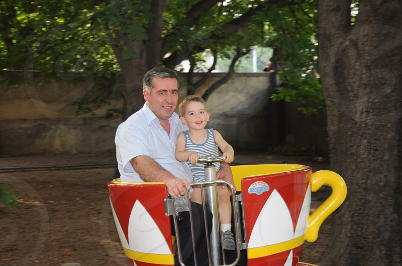 man and boy in red white and yellow park ride photo