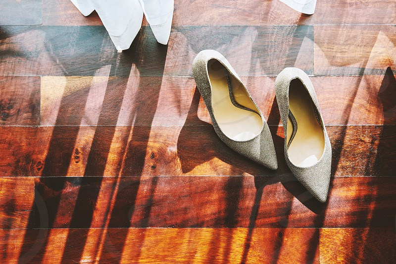 The sun light through curtain the glittering shoes with shadow on the wooden floor photo
