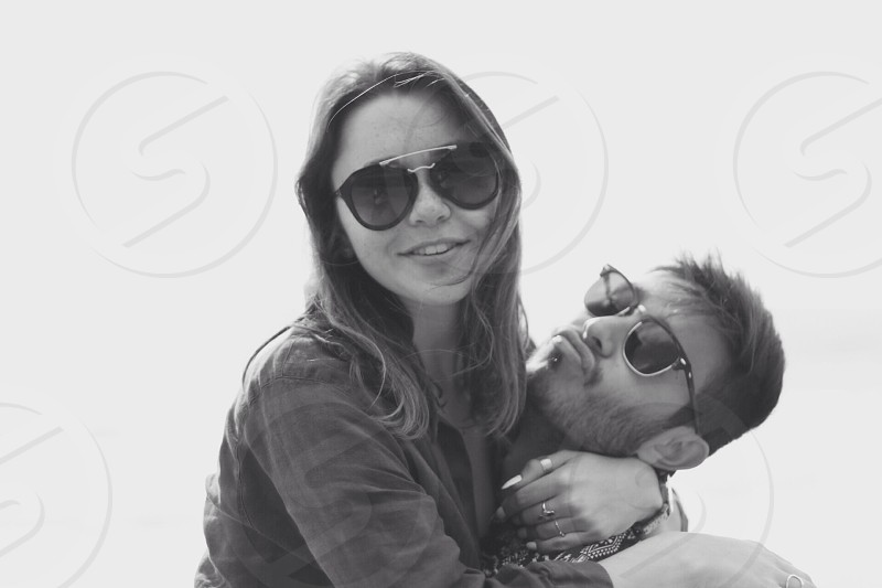 woman in sunglasses hugging man pouting lips in grayscale photo