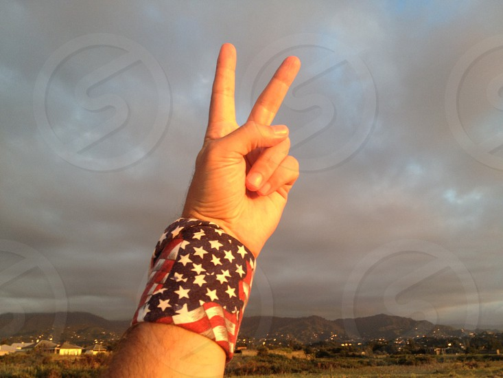 hand giving a peace sign wearing an american flag bracelet photo