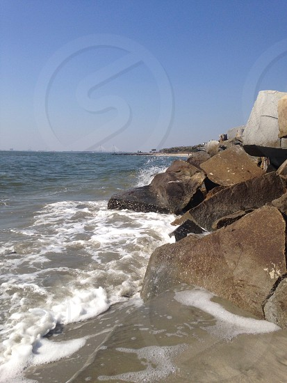 brown and block rock formation along sea photo