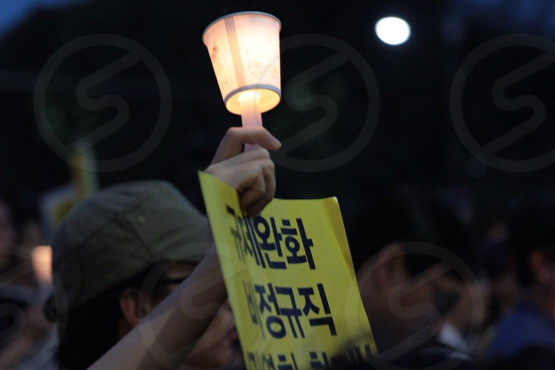 man holding light and card board with korean message photo