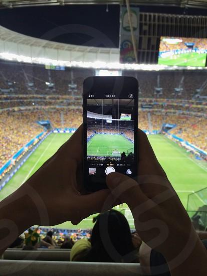person taking football arena photo