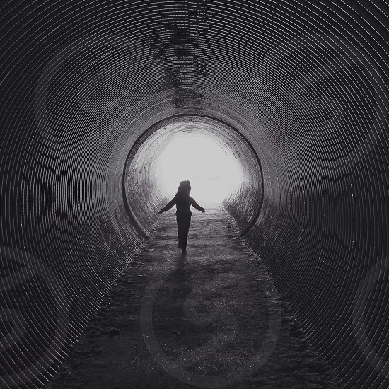 girl walking inside tunnel photo