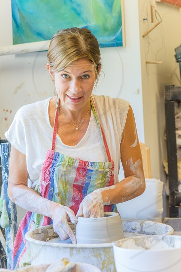 woman in white cap sleeve scoop neck shirt making clay pot photo
