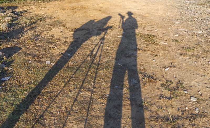 A self portrait of my and my girlfriend's shadows in early morning sunlight. Why is there no shadow of the camera that took the photo ? photo
