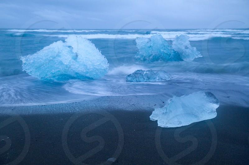 Iceland beach glacier Ice ice chunks twilight black sand water photo