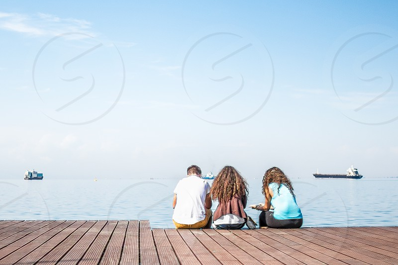 Friends Sitting On Wooden Dock photo