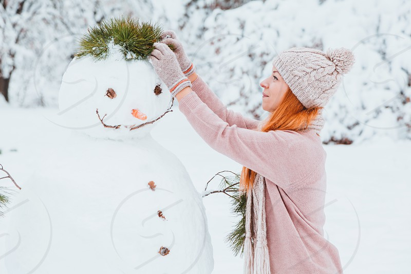 Young woman making snowman in the park photo