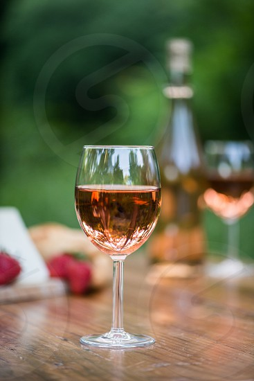 Hero shot of a glass of wine on a wooden table in an outdoor setting photo