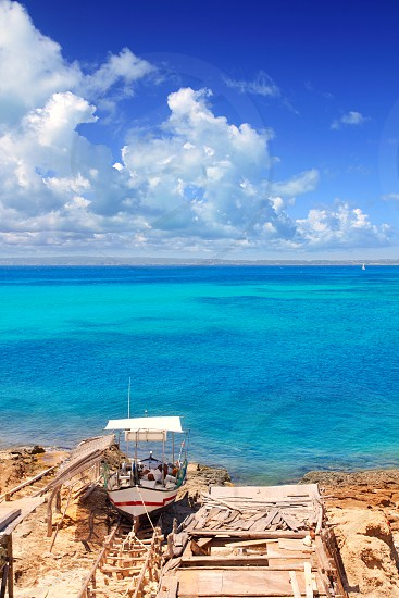 Formentera Es Ram beach with traditional boat and turquoise water photo